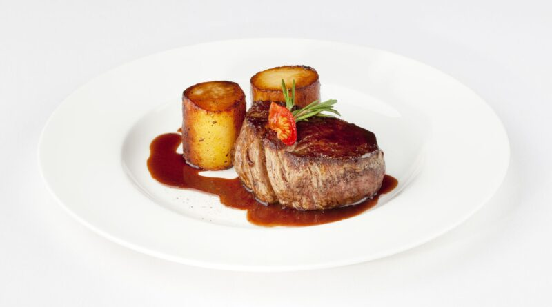 10997379 - beef filet with fondant potato and red wine sauce on a white plate bordelaise